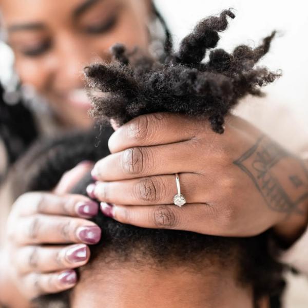 A black woman putting natural hair into a high puff