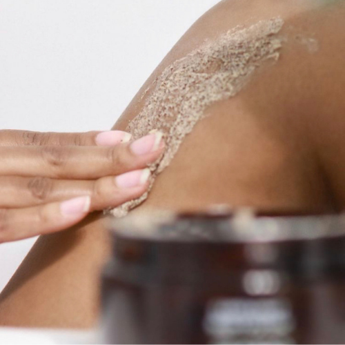 Black woman exfoliating her skin
