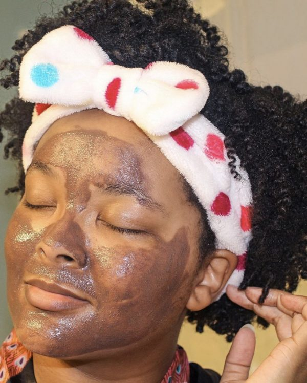 Black woman using a facial mask