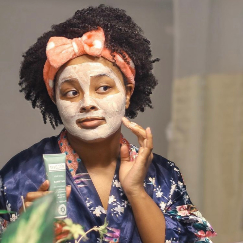 Black woman using a face mask in the mirror