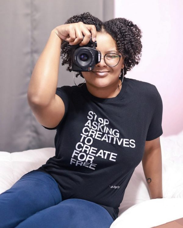 A black woman sitting on a bed while holding a Canon camera to her face