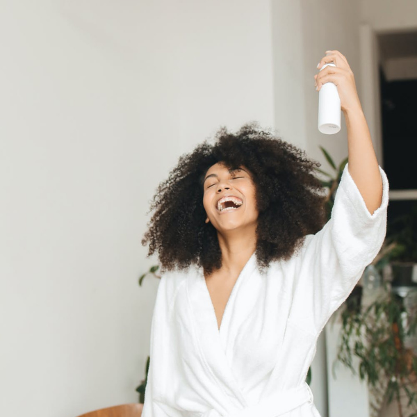 A black woman spraying water on her natural hair while smiling